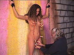 Dude attaches clothespins to bdsm brunette's small tits and shaved pussy